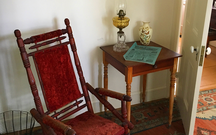 "<h3>Rocking Chair</h3> <p><strong>1700-1860</strong></p> <p>Revival style (reminiscent of Eastlake) spool turned platform rocker, maple wood construction, seat, back, and center of arms are upholstered with crushed red velvet. Front rail has red fringe. Front legs of rocker base are set on casters, rear are stationary. Two large springs on base control movement.</p> <br> <h3>Landscape</h3> <br>Charles Henry Miller</i></p><br> <p><strong>Ca. 1880-1889</strong></p> <p>Dark brooding clouds over grassy pastures with a ravine with a river on the right side.  Some indistinct people stand by the river. Charles Henry Miller was known for dark brooding pictures due to his training in Europe in the Barbazon style.</p> <br> <h3>End Table</h3> <br> <p><strong>1830-1870 <br>Gift of George R. Latham</strong></p> <p>End table with one drawer, round brass pull and turned legs, on casters.</p> <br> <h3>Kerosene Lamp</h3> <br> <p><strong>1870 <br> Gift of George R. Latham</strong></p> <p>Pressed glass kerosene lamp.  Clear two-tiered pressed glass base, brass collar piece connecting to yellow pressed glass font. Brass burner. Clear glass chimney.</p> <br> <h3>Newspaper</h3> <br> <p><strong>1882</strong></p> <p>""Farm & Fireside"" was a farming magazine active between 1878 and 1939. This edition is from October 1, 1882.</p> <br> <h3>Vase</h3> <br> <p><strong>1880-1920 <br> Gift of Ernest and Helen E. Renard</strong></p> <p>Hand painted porcelain vase. Painted with flowers and butterflies on cream colored background, each painted object outlined in gold. Gold paint around lip. Seam from mold down center sides.</p>"