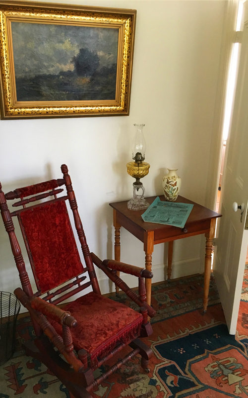"<h3>Rocking Chair</h3> <p><strong>1700-1860</strong></p> <p>Revival style (reminiscent of Eastlake) spool turned platform rocker, maple wood construction, seat, back, and center of arms are upholstered with crushed red velvet. Front rail has red fringe. Front legs of rocker base are set on casters, rear are stationary. Two large springs on base control movement.</p> <br> <h3>Landscape</h3> <p><strong>Ca. 1880-1889</strong></p> <p>Dark brooding clouds over grassy pastures with a ravine with a river on the right side.  Some indistinct people stand by the river. Charles Henry Miller was known for dark brooding pictures due to his training in Europe in the Barbazon style.</p> <br> <h3>End Table</h3> <p><strong>1830-1870 <br>Gift of George R. Latham</strong></p> <p>End table with one drawer, round brass pull and turned legs, on casters.</p> <br> <h3>Kerosene Lamp</h3> <p><strong>1870 <br> Gift of George R. Latham</strong></p> <p>Pressed glass kerosene lamp.  Clear two-tiered pressed glass base, brass collar piece connecting to yellow pressed glass font. Brass burner. Clear glass chimney.</p> <br> <h3>Newspaper</h3> <p><strong>1882</strong></p> <p>""Farm & Fireside"" was a farming magazine active between 1878 and 1939. This edition is from October 1, 1882.</p> <br> <h3>Vase</h3> <p><strong>1880-1920 <br> Gift of Ernest and Helen E. Renard</strong></p> <p>Hand painted porcelain vase. Painted with flowers and butterflies on cream colored background, each painted object outlined in gold. Gold paint around lip. Seam from mold down center sides.</p>"