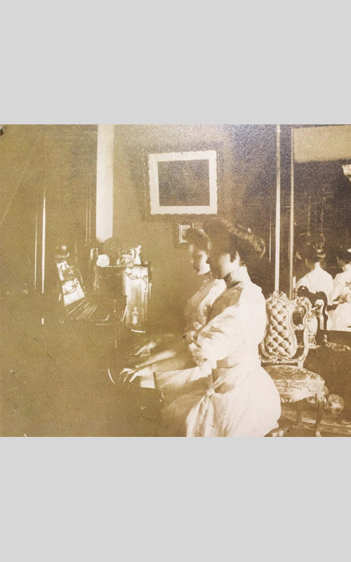 <h3>Piano Four Hands</h3> <p><i>Photographer unknown</i></p> <br> <p><strong>Ca. 1900</strong></p> <br> <br> <p>This unidentified photograph shows two women playing a single piano in a handsomely decorated house – presumably in Orient or East Marion. Like the hooked tapestry, it most likely depicts an evening musical entertainment in a private house.</p>