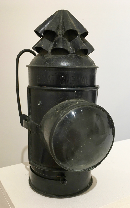 "<h3>Signal Lantern</h3> <br> <p><i>National Marine Lamp Company</i> <p><strong>Early twentieth century <br> Gift of Gabriel Latham</strong></p> <br> <br> <p>This maritime lantern was used to communicate or signal between ships or boats. There is no doubt about the use of this object: large letters just above the lens spell ""Boat Signal."" The lantern transmitted Morse code by using the sliding shutter located just beneath the door of the lamp.  This finger-operated shutter allowed or prevented light to shine through the thick, blown-glass bull's eye lens. The interior contains a removable font and burner for kerosene. This hand-held lantern has double swing bail handles at the back. There is, in addition, a mounting bracket on the back. Signal lanterns were also an essential part of the equipment found in life boats.</p>"