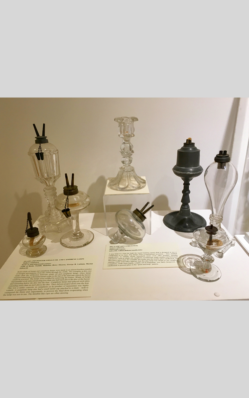 "<h3>Glass and Pewter Whale Oil and Camphene Lamps</h3> <br> <p><i>Maker unknown</i> <p><strong>Early to mid-nineteenth century <br> Gifts of Rufus Tuthill, Madeline Howe Mearns, George R. Latham, Marian Edwards</strong></p> <br> <br> <p>Both whale oil lamps and camphene lamps were made in an almost limitless number of designs and patterns from the 1830s through the 1850s. The examples in this case make clear the difference between whale oil and camphene lamps. Glass lamps required attaching a threaded metal collar to the top of the font into which the burner could be screwed. The lamps were refilled by removing the burner. Whale oil lamps had parallel wick tubes projecting less than one half inch above the disc of the burner and extending below the disc into the font.  Camphene lamps had splayed wick tubes extending more than an inch above the disc. They did not project down into the font. This was a safely concern, as camphene (a by-product of turpentine) was highly volatile. A camphene lamp also had a small metal cap attached to a chain – both to extinguish the flame and, importantly, to prevent the fluid from evaporating when the lamp was not in use. The thimble-like caps are often missing.</p> <br> <br> <hr> <br> <br> <h3>Peg Lamp and Candlestick</h3> <br> <p><i>Makers unknown</i> <p><strong>Nineteenth century <br> Gift of Dr. Lillian Dobson (Candlestick)</strong></p> <br> <br> <p>A peg lamp is a font (to hold the liquid burning agent) that is designed to use a candlestick as its base. Peg lamps were a transitional invention – they enabled candlesticks to remain useful household items even after brighter burning substances, such as whale oil, camphene, or kerosene, made candles old fashioned.  This heavy glass font, for example, fits neatly into the nearby glass candlestick. The slanting metal wick tubes indicate that this peg lamp was meant to use camphene. Camphene, made from highly volatile oil of turpentine, was fairly dangerous. The candlestick is pressed glass in the ""petal and loop"" pattern.</p>"