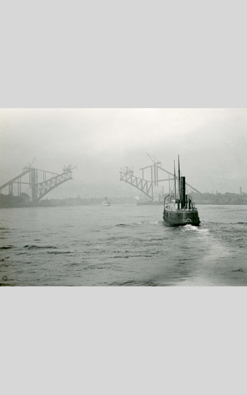 <h3>Hell Gate Bridge - Grey Morning</h3> <br> <p><i>William Steeple Davis</i><p> <br> <p><strong>1915 <br> Gift of the William Steeple Davis Trust</strong></p> <br> <br> <p>Davis made a series of photographs of the Hell Gate Bridge under construction. All were taken from the river. In this large image Davis has employed the same method he used for one of his photographs of the Queensboro Bridge: he waited for the perfect moment when a boat appeared that would both lead the eye into the picture, and at the same time furnish a note of tonal contrast.  The Hell Gate Bridge, built as a railroad bridge, was the crucial link for train service between Washington and Boston. Designed by the engineer Gustav Lindenthal and the architect Henry Hornbostol, it was completed in 1917 – exactly one hundred years ago. This impressive structure over a dangerous stretch of the East River was the inspiration for the Sydney Harbor Bridge in Australia. Note Davis's stamp in the lower left-hand corner; this usually indicates that this print was either sent to a publication or an exhibition.</p>