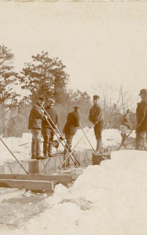 <h3>Ice Cutting, East Marion</h3> <br> <p><i>Photographer unknown</i></p> <strong>Ca. 1900</strong> <br> <br> <p>This photograph shows the west side of East Marion Lake with men pushing out ice through a sluiceway.</p>