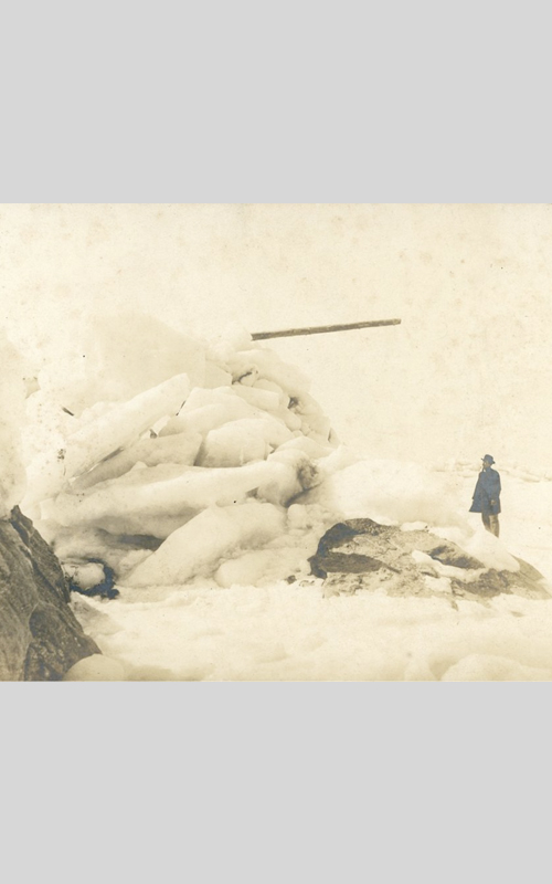 <h3>Ice on the Sound Rocks</h3> <br> <p><i>W.H. Vail</i></p> <strong>Ca. 1900</strong> <br> <br> <p>H. Vail, a fisherman in Orient, took a group of wonderful photographs around the turn of the last century. Many were of the boat and crew of the Black Eagle, a well-known fishing boat owned by members of the Vail family. This land-based photograph shows how severe the winters could be in Oysterponds. Is that a boat spar sticking out above the enormous pile of ice? The ice dwarfs D. Milton Rackett who is shown standing nearby.</p>