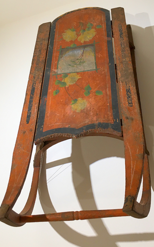 <h3>Sled</h3> <br> <p><i>Maker Unknown</i></p> <br> <strong>Late nineteenth / early twentieth century</strong> <br> <br> <p>This colorful red sled has black stripes and yellow roses surrounding a tree that is painted in the center portion of the sled. Although the flexible flyer – a steerable sled – was invented as early as the 1880s, there were still many ordinary sleds like this one produced. They were often decorated, though were usually not as fanciful as the OHS sled. A sled like this one has become an iconic piece of Americana thanks to Orson Welles' film <i>Citizen Kane.</i></p>
