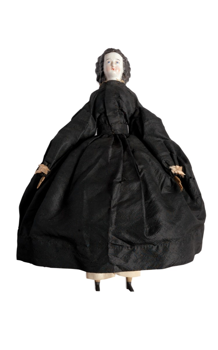 <h3>Civil War Widow Doll</h3> <br> <p><strong>Porcelain, Wood, Silk, Cotton, Wire</strong></p> <p><strong>Ca. 1865</strong></p> <p><strong>Gift of Ruth and Jean Schneider</strong></p> <br> <p>This very fine doll with her porcelain face, black hair, wooden hands, legs and feet, and a body made of cloth, sits dates well within the time frame of the Civil War. It has traditionally been identified as representing a Civil War widow. The clothes are the significant feature of this doll and her entire ensemble is very neatly made – most notably a wire hoop to support the fashionably full skirt of the fine black silk dress. A large and beautifully-made parasol completes her outfit. The doll's costume carefully copies the practical custom of the period having cuffs and collar which could be easily removed for washing. Note that the figure of the grieving woman at the grave in the lithograph to the right is wearing a dress identical to that of the doll. This Civil War doll once belonged to William Steeple Davis who most likely inherited it from his mother Carrie Hubbard Davis.</p>