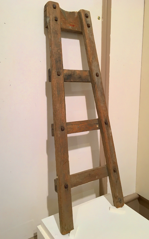 <h3>Lamplighter's Ladder</h3> <br> <p><i>Maker unknown</i><p> <br> <p><strong>Late nineteenth/early twentieth century <br> Gift of Mrs. Edgar Brown</strong></p> <br> <br> <p>This framed wooden ladder with three steps has a curved section cut from the top stretcher so the ladder would be stable against a round post. This was the ladder actually used in Orient by the lamplighter. The lamps were made by the Dietz Company; an example of the lamp frame and glass globe can be seen if you look out the door towards the street. At the end of the walk – by the sidewalk – is an original Orient street lamp.</p>