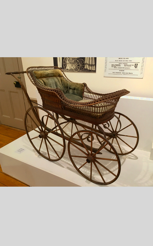 <h3>Baby Carriage</h3> <br> <p><i>Maker unknown</i><p> <br> <p><strong>Ca. 1890 <br> Gift of Mrs. Wentworth Horton</strong></p> <br> <br> <p>Beginning in the 1870s and 1880s wicker became the material of choice for baby carriages. Wicker was lightweight yet strong and could be formed into wonderfully inventive and extravagant shapes. Wicker's light and airy quality was seen to be a reflection of a new attitude towards healthy living. Wicker, or rattan, as an industry was an American phenomenon and the material was used for every conceivable sort of household object. The largest wicker producers were in Massachusetts, but interestingly there was a wicker factory in Greenport beginning in the late 1880s.  A book by Elsie Knapp Corwin and Frederick Langton Corwin quotes an item from the Suffolk Times: <i>The Greenport Rattan Company, since its organization, has been pushing steadily forward in the manufacture of baby carriages, chairs, small tables and all the accompanying products of a rattan factory. Heretofore the carriage bodies only, have been furnished here, the other fittings and upholstery being done in New York. But now the company has completed arrangements so that the carriages are made complete, upholstered in any color – to suit the baby's complexion – and sold for less than they can be bought in New York. This baby carriage, in excellent condition, might well have been made in Greenport.</i></p>