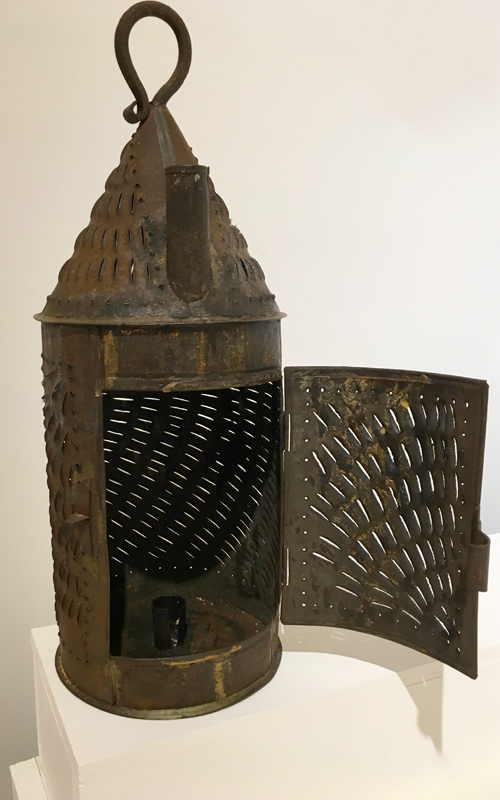 <h3>Pierced Tin Lantern</h3> <p><strong>Nineteenth century <br> Gift of George R. Latham</strong></p> <p>In this type of tin lantern the candle is fully enclosed, so it would not be extinguished when the lantern was carried outside on a windy night.  Before electricity this was an important consideration if, for example, a person went to the barn or visited the privy.  An enclosed candle was also much safer than an exposed candle; barns for example were filled with flammable materials. If more light was needed, and fire was not an issue, the door of the lantern could be opened to throw out more light. The chimney-like protrusion at the top was a candle holder; the candle – or an additional one – could be placed there if additional light was needed. Lanterns like this had a conical top and a looped hanging device. They are often called Paul Revere lanterns, but the connection to Revere is tenuous at best.</p>