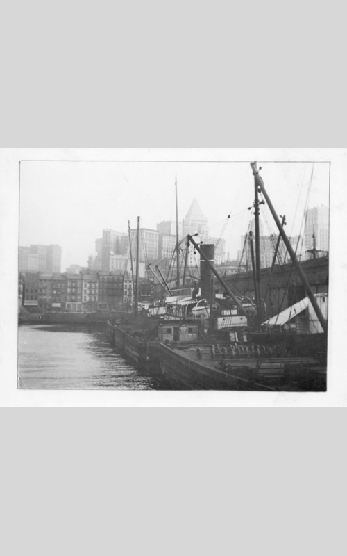 """<h3>At a New York Pier</h3> <br> <p><i>William Steeple Davis</i><p> <br> <p><strong>Ca. 1914 <br> Gift of the William Steeple Davis Trust</strong></p> <br> <br> <p>A notation on the back of the photograph states that this view is of the """"Munson Line, Pier 9, East River, New York."""" The slightly different title above was used when Davis sent the photograph to The Camera magazine, although there is nothing to indicate whether or not it was published. The photograph depicts a stark contrast of old and new. The city of tall buildings appears to rise up dream-like behind the early nineteenth-century buildings at the river's edge. The pile up of the tall buildings, rendered so light in tone that they almost disappear, culminate in the pyramidal roof of the Bankers Trust Building of 1912 which was a startling addition to the New York skyline. It was said to be modelled on the Mausoleum of Halicarnassus, one of the seven wonders of the ancient world.</p>"""
