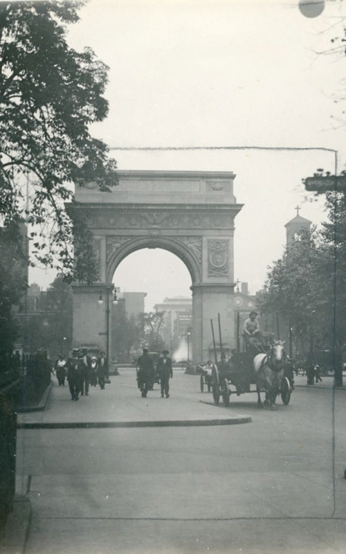 """<h3>Washington Square Arch - Looking South</h3> <br> <p><i>William Steeple Davis</i><p> <br> <p><strong>Ca. 1915 <br> Gift of the William Steeple Davis Trust</strong></p> <br> <br> <p>This photograph won third prize in a Photo-Era magazine """"Street Scenes"""" contest. Although the photograph focuses on the famous arch at the beginning of New York's grandest avenue, it encompasses a New York summer scene with men in straw boater hats, a woman in an open carriage, a horse-drawn cart, and a fountain playing in the background. The tower of the Judson Memorial Church designed by McKim, Mead & White and completed in 1896 can be seen in the background at the far right. The arch itself was designed by Stanford White and commemorates the inauguration of George Washington as president of the United States. (This permanent arch in marble followed the original arch made of wood and plaster which was erected in 1889 to commemorate the centennial of that event). Note that Davis has marked in pencil where he planned to make a tighter version of this photograph. He frequently re-worked an image – both for scale and for atmospheric effects.</p>"""