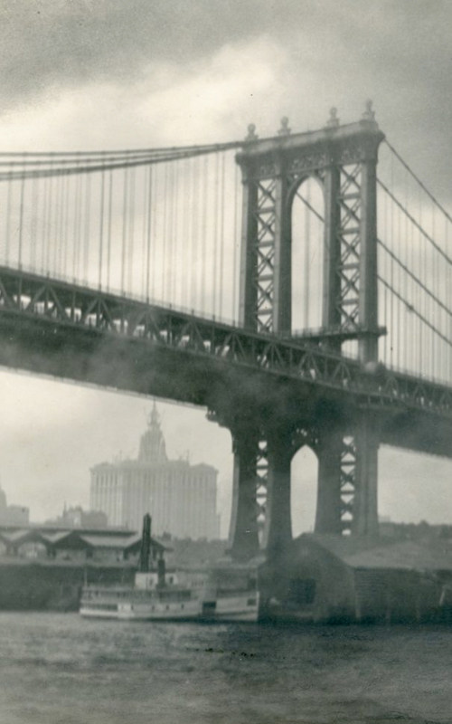 """<h3>Manhattan Bridge</h3> <br> <p><i>William Steeple Davis</i><p> <br> <p><strong>Ca. 1914 <br> Gift of the William Steeple Davis Trust</strong></p> <br> <br> <p>In 1915 Davis published an article in Photo-Era magazine titled """"Bridges as Pictorial Subjects."""" In it he writes: """"to gain the clearest impression of the size [of the bridge] it must be seen from below."""" He goes on to say that the """"massive bulk… is best realized when the atmospheric conditions and lighting are such as to isolate the structure somewhat from its environment."""" Here the Manhattan Bridge, which was opened in 1909, is shown from river level while the two prominent buildings in the background are shrouded in fog or mist. Those buildings are, at the far left, the Woolworth Building, completed in 1913, and the Municipal Building which opened a year later in 1914.</p>"""