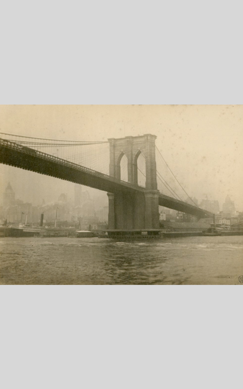 """<h3>The Brooklyn Bridge</h3> <br> <p><i>William Steeple Davis</i><p> <br> <p><strong>Ca. 1914  <br> Gift of the William Steeple Davis Trust</strong></p> <br> <br> <p>The Brooklyn Bridge, a marvel of nineteenth-century engineering and one of the great bridges of the world, was completed in 1883.  Davis, born a year after the bridge was completed, was inspired by the bridge even as a child (see the drawing in the case in this gallery). In his article in Photo-Era magazine titled """"Bridges as Pictorial Subjects"""" Davis discusses this photograph and writes: """"The exposure being made from a steamer's deck one morning during a fog, which, while giving a suggestive glimpse of the Manhattan sky-scrapers, produced the necessary differentiation of tone to emphasize the mass of the bridge."""" This photograph was mounted by Davis and is signed with his stamp which suggests it was made to be exhibited.</p>"""