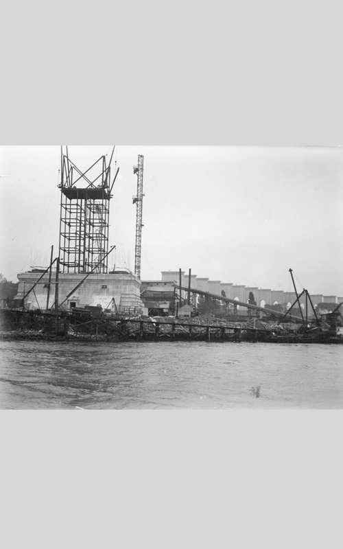 """<h3>Hell Gate Bridge Under Construction</h3> <br> <p><i>William Steeple Davis</i><p> <br> <p><strong>1914 <br> Gift of the William Steeple Davis Trust</strong></p> <br> <br> <p>Davis has written on the back of this photograph: """"Piers of new Hell-Gate Bridge."""" He seems to have taken a particular interest in the construction of this important bridge as several other photographs in the exhibition demonstrate. The designer of the bridge, Gustav Lindenthal, was New York City's first bridge commissioner. The grand sweep of the viaducts carrying the approaches to the bridge is impressive, but the main focus here is the construction of one of the great piers or towers. Lindenthal's grandson was recently quoted as saying that """"the stone towers are really only decorative. They don't have any structural function. But he had those stone towers built because he felt they made [the bridge] look right.""""</p>"""