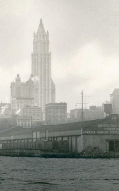 """<h3>The Woolworth Tower</h3> <br> <p><i>William Steeple Davis</i><p> <br> <p><strong>Ca. 1914  <br> Gift of the William Steeple Davis Trust</strong></p> <br> <br> <p>This is an example of Davis's creative process at work. Compare this image with the photograph titled """"East River Waterfront – New York"""" on view in this gallery. This is simply an enlarged center section of that photograph. Davis, after developing the original photograph, would manipulate the image in the darkroom by cropping, enlarging, or perhaps """"printing in"""" clouds and other atmospheric details before sending the resulting image to an exhibition or publication. The Woolworth Building, designed by the architect Cass Gilbert, was the tallest building in the world when it opened in 1913 shortly before this photograph was made. Owing to its Gothic ornamentation, the Woolworth Building became known as the """"Cathedral of Commerce."""" The photograph was exhibited at the Toronto Salon in 1923.</p>"""