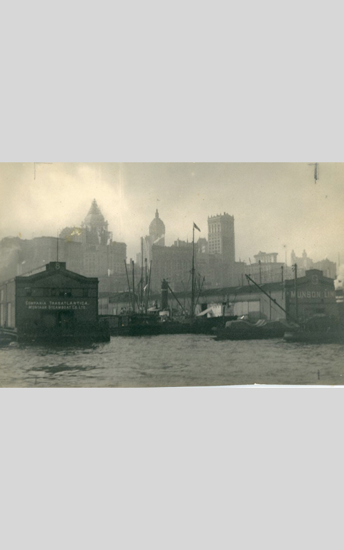 <h3>New York Harbor - Munson Pier</h3> <br> <p><i>William Steeple Davis</i><p> <br> <p><strong>Ca. 1911  <br> Gift of the William Steeple Davis Trust</strong></p> <br> <br> <p>This photograph is dated slightly earlier than many in this exhibition, as the Bankers Trust Building (the tall building under construction on the left) was not completed until 1912. There are two very similar versions of this image in the exhibition; together they illustrate how Davis would make changes in the darkroom – sometimes very slight – to the image. This print has pencil lines at the top indicating how Davis plans to crop the photograph in the other version. What is particularly noteworthy in this print is the rich black of the foreground buildings making this photograph look similar to a mezzotint.  Whether or not Davis had a favorite version we do not know. He sent this one to Photo-Era magazine where it was published in September 1915.</p>