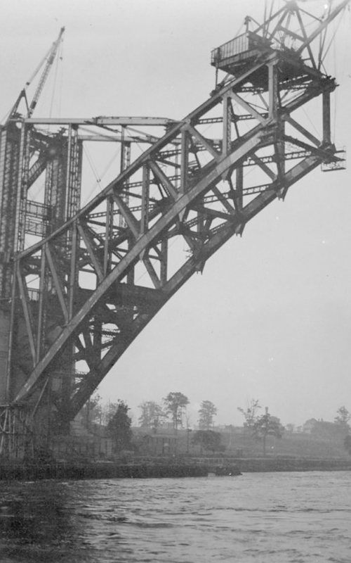 """<h3>Under Construction</h3> <br> <p><i>William Steeple Davis</i><p> <br> <p><strong>1915 <br> Gift of the William Steeple Davis Trust</strong></p> <br> <br> <p>This photograph of the Hell Gate Bridge was titled """"Under Construction"""" when it appeared in Davis's article """"Bridges as Pictorial Subjects"""" in the September 1916 issue of Photo-Era magazine. Davis writes about how clouds were """"printed in…to complete the tone and line composition of 'Under Construction,' a study of the great arch of the Hell Gate Bridge as it appeared in August, 1915."""" The Hell Gate Bridge over the East River was a railroad bridge which enabled rail traffic to get to Boston from New York without changing stations. It was opened in 1917. An impressive bridge that conveys a sense of great power and strength, it was the inspiration for the Sydney Harbor Bridge in Australia. The chief designer of this bridge was Gustav Lindenthal.</p>"""