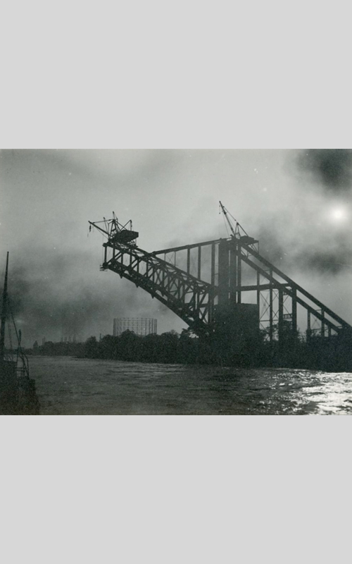 """<h3>The Building of the Bridge</h3> <br> <p><i>William Steeple Davis</i><p> <br> <p><strong>1915 <br> Gift of the William Steeple Davis Trust</strong></p> <br> <br> <p>This particularly evocative photograph of the Hell Gate Bridge was taken by Davis in the summer of 1915 when the extraordinary structure was about two-thirds complete. One of Davis's editors at Photo-Era magazine wrote about his photographs of the Hell Gate Bridge: """"I can well appreciate how deeply impressed Mr. Davis must have been by the pictorial and dramatic appeal of this remarkable and beautiful bridge."""" Although small in scale, this photograph presents a powerful image of New York at a moment when the city was building one after another the largest and highest structures in the world. Davis was keen on moonlight photography, and here has added an aura of mystery to the image. A re-worked version of this same photograph won third prize in a contest sponsored by Photo-Era in August 1922.</p>"""