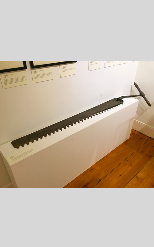 <h3>Ice Saw</h3> <br> <p><i>Maker unknown</i></p> <strong>Ca. 1900</strong> <br> <br> <p>Large saws like this were used in ice cutting at East Marion Lake. An ice saw for a lake or pond is very long because it has to be able to cut through ice that might be twelve to eighteen inches thick. It has a double grip handle made of wood and screwed to the iron saw handle. (The handle of the saw on view has been turned in the same line as the blade for display; ordinarily it would be perpendicular to the blade).   This very long blade has extra-large teeth for easier cutting.</p>