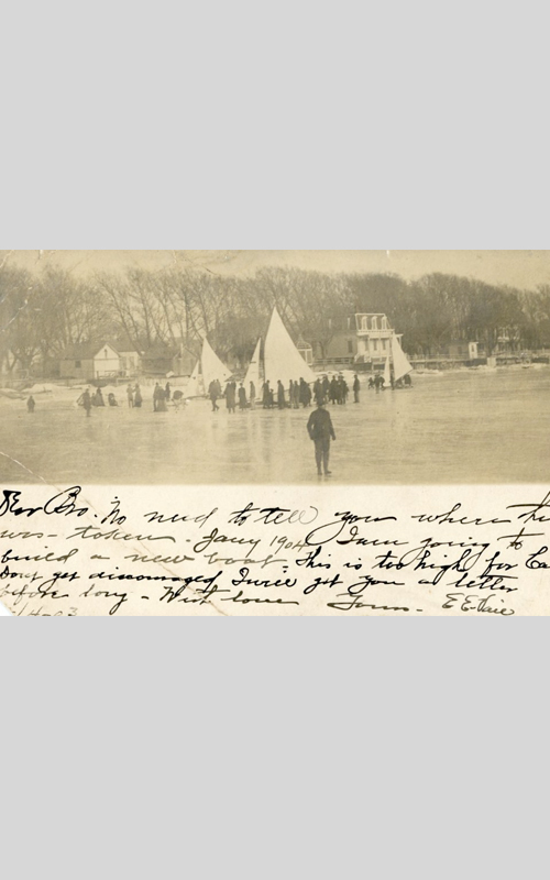 """<h3>Winter Scene, Orient</h3> <br> <p><i>Photographer unknown</i></p> <strong>Ca. 1904</strong> <br> <br> <p>This festive winter scene on the ice in Orient Harbor near the wharf was taken in January, 1904. The mansard-roofed house in the background is still very much a feature of the harbor view. The image was made into a postcard and sent by E.E. Vail to his brother W.H. Vail in California in February of 1904.  He writes: """"No need to tell you where this was – taken Jany 1904. I am going to build a new boat. This is too high….""""</p>"""