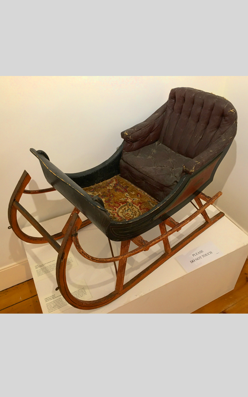 <h3>Child's Sleigh</h3> <br> <strong>Nineteenth Century <br> Gift of Violet Dearborn Latham</strong> <br> <br> <p>This beautifully painted child's sleigh is in excellent condition. With its well-preserved leather seat and colorful rug it seems to have been little used over the years. This is a pull sleigh as opposed to a push sleigh. Push sleighs are like baby carriages with a large handle at the back for an adult to push the sleigh along the snow-covered paths or roads. A pull sleigh like this one might have been pulled along by an animal such as a pony, a dog, or a goat – or by a human such as a parent or an older sibling.</p>