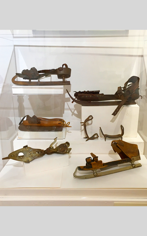 """<h3>Group of Ice Skates and Pair of Ice Creepers</h3> <br> <strong>Nineteenth Century <br> Gift of various donors</strong> <br> <br> <p>The adjustable skate at the bottom left is marked """"Peck & Snyder's American Club."""" Peck & Snyder Sporting Goods Company was one of the first and best known sporting goods manufacturers in the U.S. The American Club skate was first made in 1873. Note the unusual curved shape of the sole of the skate at the upper left. At the middle right is a pair of ice creepers; this pair was probably made by a local blacksmith. They are designed to strap on around a person's shoes to firmly grip the ice and are known by a variety of names such as crampons, ice cleats, and spikes.</p>"""