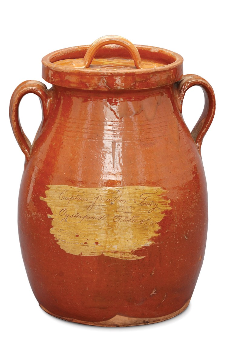 """<h3>REDWARE DOUBLE-HANDLED POT WITH LID</em></h3> <br> <p><strong>Maker unknown</strong></p> <p><strong>1800</strong></p> <p><strong>Gift of Irving Latham and Marion L. Edwards</strong></p> <br> <p>This is the most important ceramic in the Oysterponds Historical Society collection. It is clearly marked in a handsome script with a name and a date: Captain Jonathan Terry / Oysterponds / October 6th 1800. It was most likely made on eastern Long Island or Connecticut. There is another almost identical piece in the collection of the Winterthur Museum and Country Estate in Delaware which has an inscribed date just one day later than this pot: Octr 7 1800. The remainder of that inscription reads: Mr. Silas Ruiment / Sag-Harbour – Long Island. Captain Jonathan Terry was born in 1770 and died in 1820. Augustus Griffin in his Journal writes that he and his brother """"for many years sailed handsome coasting vessels from this village."""" There have been Terrys in Oysterponds since the seventeenth century.</p>"""