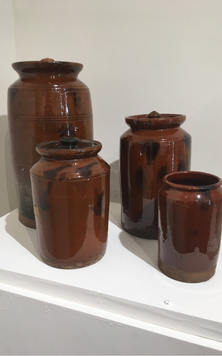 <h3>FOUR REDWARE STORAGE JARS</em></h3> <br> <p><strong>Made by the Hempstead Pottery in Greenport</strong></p> <p><strong>Ca. 1850</strong></p> <p><strong>Gifts of Curt Tabor and others</strong></p> <br> <p>Although unusual for its size, the tallest jar here is an excellent example of Greenport redware. Frequent misfiring of the lead glazes created an orange-brown color that is typically identified with the Hempstead Pottery in Greenport which was located on Sterling Harbor. The smaller example on the left was also made in Greenport. Although all four storage jars can be attributed to the Greenport pottery, the two on the right are more difficult to positively identify. The smallest could be from Norwalk, Connecticut, and the other might have been made in Huntington (although its lid is certainly Greenport).</p>