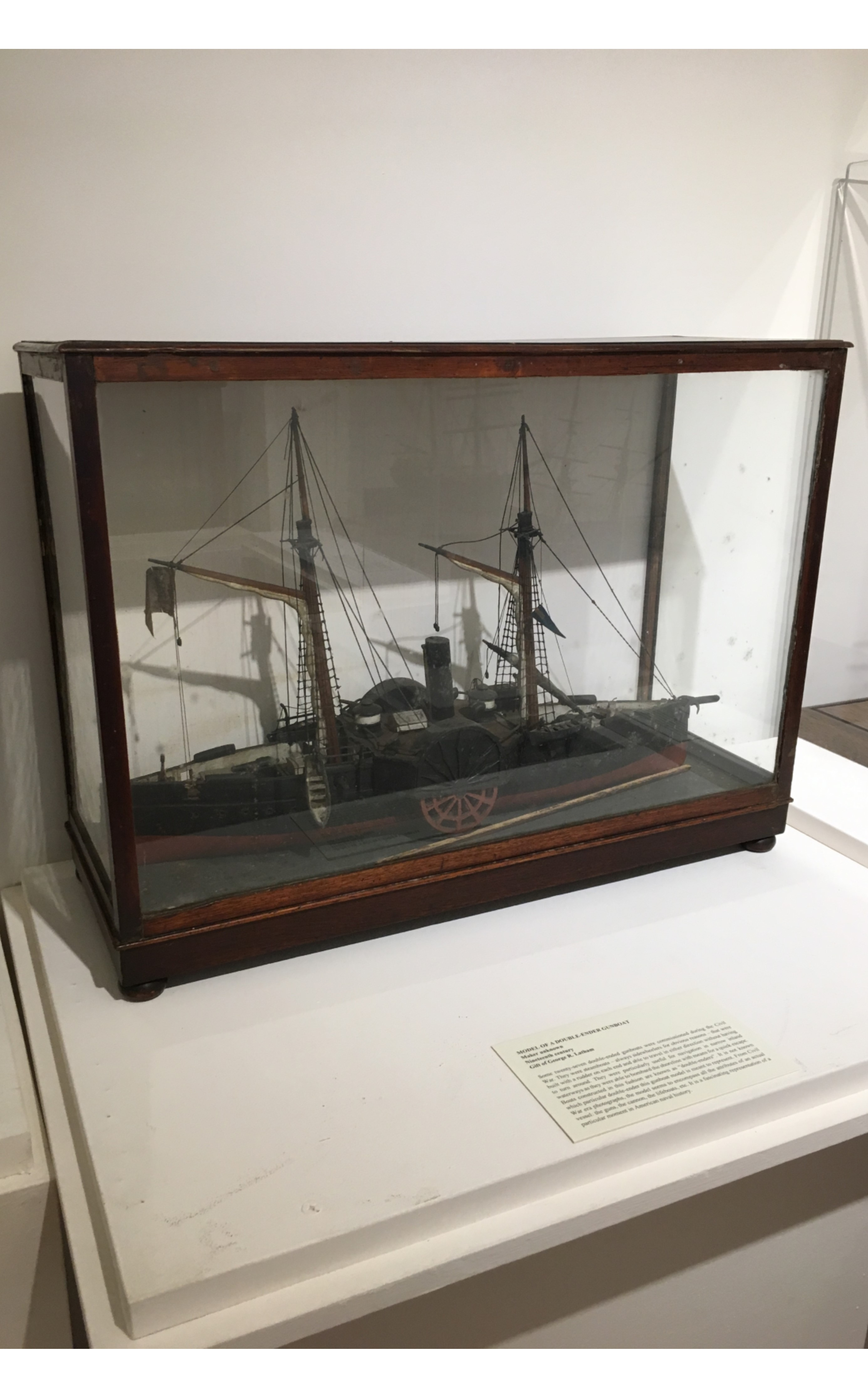 """<h3>MODEL OF A DOUBLE-ENDER GUNBOAT</em></h3> <br> <p><strong>Maker unknown</strong></p> <p><strong>Nineteenth century</strong></p> <p><strong>Gift of George R. Latham</strong></p> <br> <p>Some twenty-seven double-ended gunboats were commissioned during the Civil War. They were steamboats – always sidewheelers for obvious reasons – that were built with a rudder on each end and able to travel in either direction without having to turn around. They were particularly useful for navigation in narrow inland waterways as they were able to bombard the shoreline with means for a quick escape. Boats constructed in this fashion are known as """"double-enders"""". It is not known which particular double-ender this gunboat model is meant to represent. From Civil War era photographs, the model seems to encompass all the attributes of an actual vessel: the guns, the cannon, the lifeboats, etc. It is a fascinating representation of a particular moment in American naval history.</p>"""