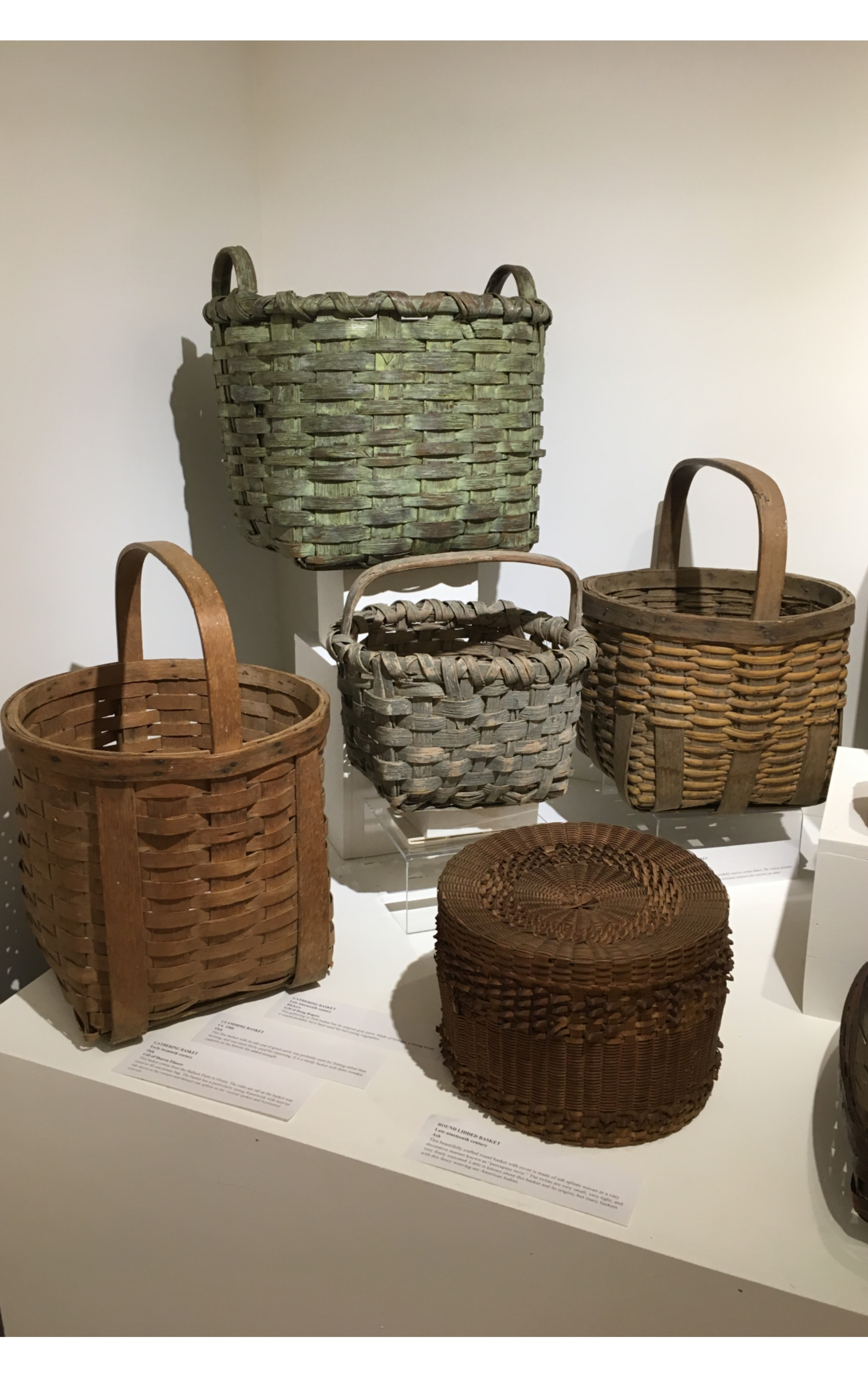 """<h3>GATHERING BASKET</em></h3> <br> <p><strong>Oak</strong></p> <p><strong>Early-twentieth century</strong></p> <p><strong>Gift of Sharon Elmore</strong></p> <br> <p>This basket comes from the Hallock Farm in Orient. The sides are tall as the basket was sized to fill one potato bag. The basket has a particularly strong framework with heavier oak staves at the corners and thinner oak splints as the vertical spokes and horizontal weavers.</p> <br> <br> <hr> <br> <br> <h3>CLAMMING BASKET</em></h3> <br> <p><strong>Oak</strong></p> <p><strong>Ca. 1900</strong></p> <br> <p>This fine basket with its old coat of green paint was probably used for fishing rather than farming, and was most likely used for clamming. It is a sturdy basket with three wooden supports on the bottom for added strength.</p> <br> <br> <hr> <br> <br> <h3>GATHERING BASKET</h3> <br> <p><strong>Hickory</strong></p> <p><strong>Late-nineteenth century</strong></p> <p><strong>Gift of Doug Rogers</strong></p> <br> <p>This gathering or field basket has its original gray paint. Made of hickory, a strong wood, it would probably have been used for harvesting vegetables.</p> <br> <br> <hr> <br> <br> <h3>ROUND LIDDED BASKET</h3> <br> <p><strong>Ash</strong></p> <p><strong>Late-nineteenth century</strong></p> <p><strong>Gift of George Terry</strong></p> <br> <p>This beautifully crafted round basket with cover is made of ash splints woven in a very decorative manner known as """"porcupine twist."""" The twists are very small, very tight, and very finely executed. Little is known about this basket and its origins, but many baskets with this fancy weaving are American Indian.</p> <br> <br> <hr> <br> <br> <h3>GATHERING BASKET</h3> <br> <p><strong>Oak and Rattan</strong></p> <p><strong>Ca. 1900</strong></p> <p><strong>Gift of Irma Hupfel</strong></p> <br> <p>This gathering or field basket was probably used as a potato basket. The vertical elements (the spokes) are made of oak and the horizontal elements (the weavers) are ratta"""