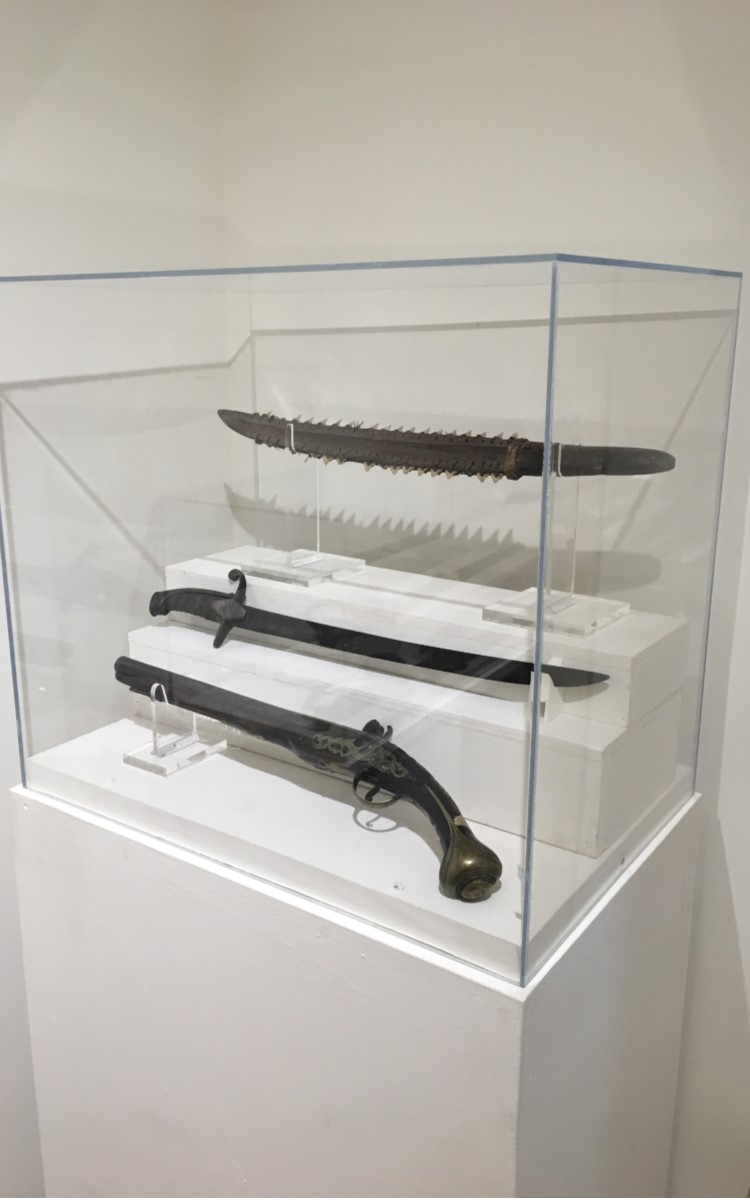 <h3>Shark's Teeth Saber</h3> <br> <p><strong>Nineteenth century</strong></p> <p><strong>Gift of Harold Latham</strong></p> <br> <p>This lethal weapon from the South Pacific was very likely brought home from a whaling voyage. Some of the shark teeth have been broken or are missing, but nine shark teeth on one side and seventeen on the other still remain. This finely-crafted saber with a pronounced ridge at the center of the blade is made of wood. The edges have a carved slot running the length of the blade into which the shark teeth are inserted. Each tooth has a drilled hole and is tied to the surface of the saber with sennit, a type of twine likely made of coconut fiber. As shark teeth are very strong and resistant to wear, skilled craftsmanship was required to drill the holes. Each tooth is tied to the blade through either one or two holes drilled through the wood. Sennit cordage is wrapped around the handle where the blade begins.</p> <br> <br> <hr> <br> <br> <h3>Sword</h3> <br> <p><strong>Late eighteenth century</strong></p> <p><strong>Gift of Elsie Ketcham</strong></p> <br> <p>This short sword has a wired wooden hilt with top edge brass overlay. Tradition has it that this weapon was made by a soldier in the Continental Army from parts of German hanger and a British hanger.</p> <br> <br> <hr> <br> <br> <h3>Flintlock Pistol</h3> <br> <p><strong>Maker unknown</strong></p> <p><strong>Firts half of the nineteenth century</strong></p> <p><strong>Gift of Captain and Mrs. Frank Tuthill</strong></p> <br> <p>This flintlock pistol was owned by Hull Conklin and used by him on the first stagecoach between Oysterponds and Brooklyn. That stagecoach was in operation until 1844 when the first train arrived in Greenport. The pistol was donated in 1945 and was one of the first few gifts to the newly-formed Oysterponds Historical Society.</p>