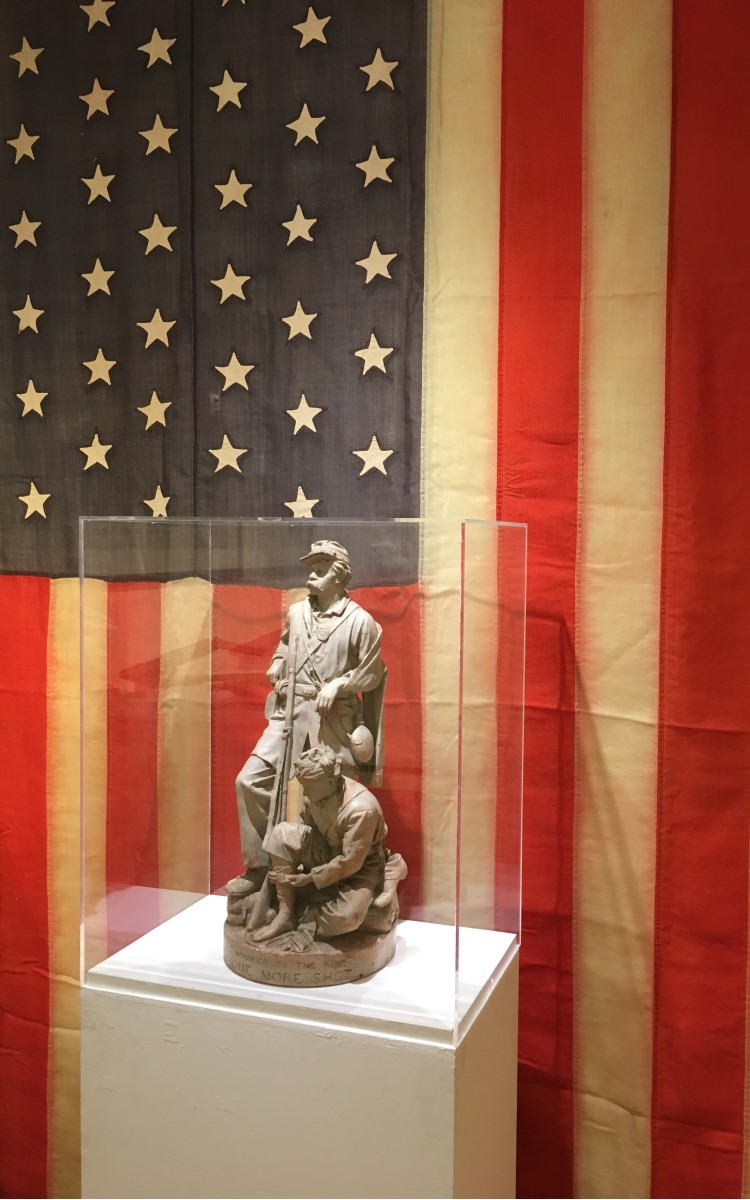 """<h3>American Flag</h3> <br> <p><strong>1864-1867</strong></p> <p><strong>Gift of Philip and Anne Calderone in memory of Philip J. Calderone, US Marine & Korean War Veteran</strong></p> <br> <p>Nevada entered the Union as the 36th state on October 31, 1864, but the 36-star flag did not become official until July 4, 1865 – two months after the Civil War had ended on May 9, 1865. Even so, some military units did use the 36-star flag during the course of the war. The 36-star flag was in use for just two years – until Nebraska became a state in 1867. The only president to serve under the flag was Andrew Johnson.</p> <br> <p>The name Smith Sprague is written on the flag, but the specific history of that name and this flag is unknown. The flag was found on Long Island and authenticated by the Smithsonian Institution for the local donors.</p> <br> <br> <hr> <br> <br> <h3><em>Wounded to the Rear, One More Shot</em></h3> <br> <p><strong>John Rogers</strong></p> <p><strong>1864</strong></p> <br> <p>This painted plaster sculpture is by John Rogers (1829-1904) one of the best-known artists of the Civil War era. He specialized in plaster groups such as this and sold an enormous number of them – reputedly some 80,000 in all. He produced sculptural groups on a variety of subjects, including many about the Civil War. This particular group - with the title of the work clearly inscribed at the base of the sculpture - is called: """"Wounded to the Rear, One More Shot"""". It is considered the most successful of all his Civil War groups. When it went on sale in November of 1864 it became immediately popular thanks to its subject matter. Rogers himself described this work: """"Two wounded soldiers have been ordered to the rear during a battle, but one of them is taking out a cartridge to load up again, determined to have one more shot before leaving."""" The standing soldier stares defiantly at the enemy as he reaches for his ammunition. His left arm is in a sling; his companion sits below binding u"""