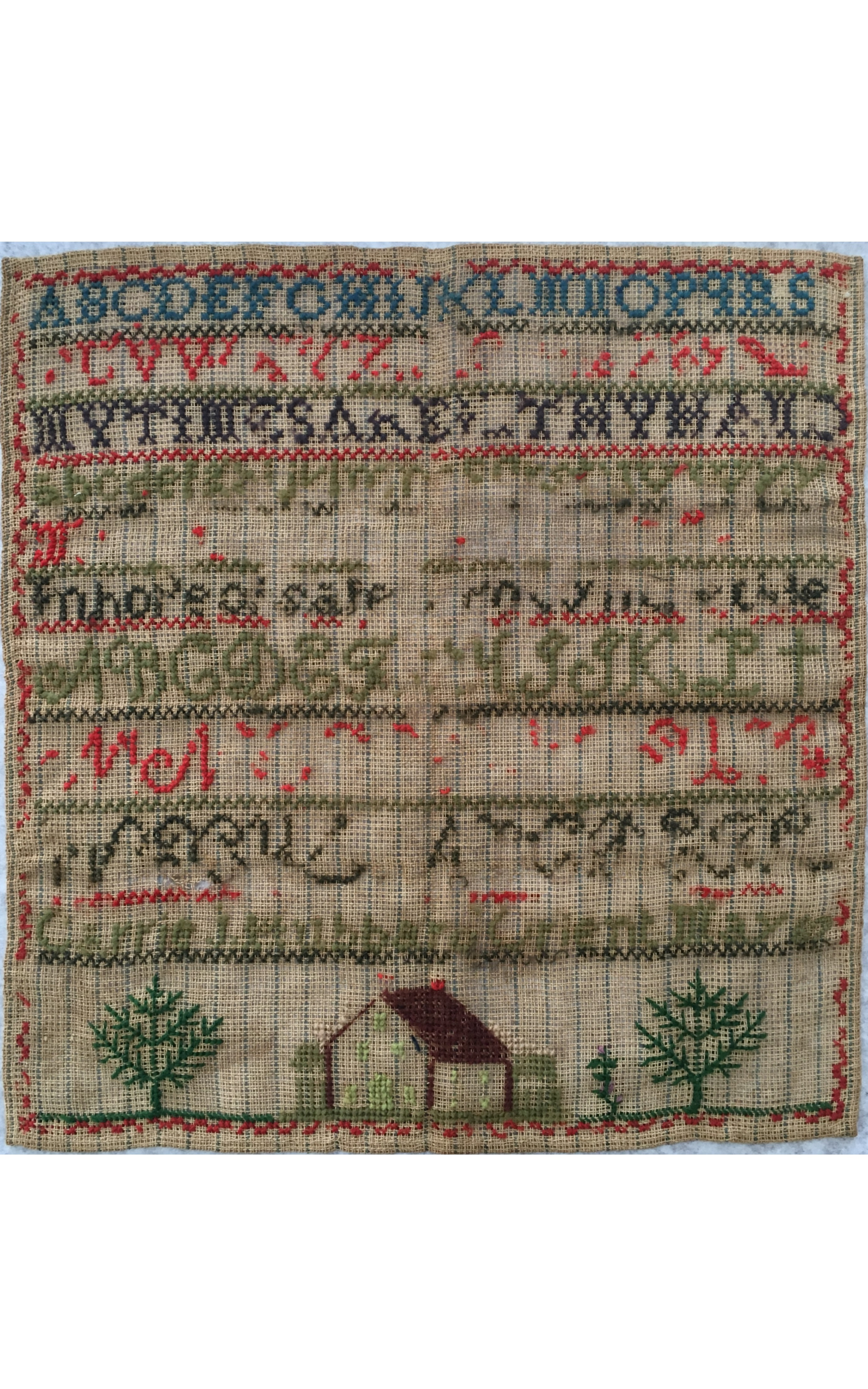 """<h3>Carrie J. Hubbard Sampler</h3> <br> <p><strong>Ca. 1865</strong></p> <p><strong>Gift of William Steeple Davis</strong></p> <br> <p>This sampler was made by the mother of William Steeple Davis (1884-1961), an artist and photographer who lived his entire life in Orient. A very large collection of his photographs, paintings, childhood drawings, etc. form an important part of the holdings of OHS. His mother, Carrie (1853-1950), the daughter of Jane Culver Hubbard and Smith Hubbard, grew up in Orient and made this sampler when she was fourteen years old. On the last line, she has stitched her name followed by """"Orient 67"""". Several sections of the sampler have virtually disappeared, but fortunately her name and charming depiction of trees and a house remain legible. Carrie Hubbard Davis is the subject of the book, <em>Captain's Daughter, Coasterman's Wife</em>, written by Joan Druett and published by OHS in 1995. She is also featured prominently in a book about her mother, <em>In Her Own Name</em>, written by Fredrica Wachsberger and published in 2015 by OHS.</p>"""