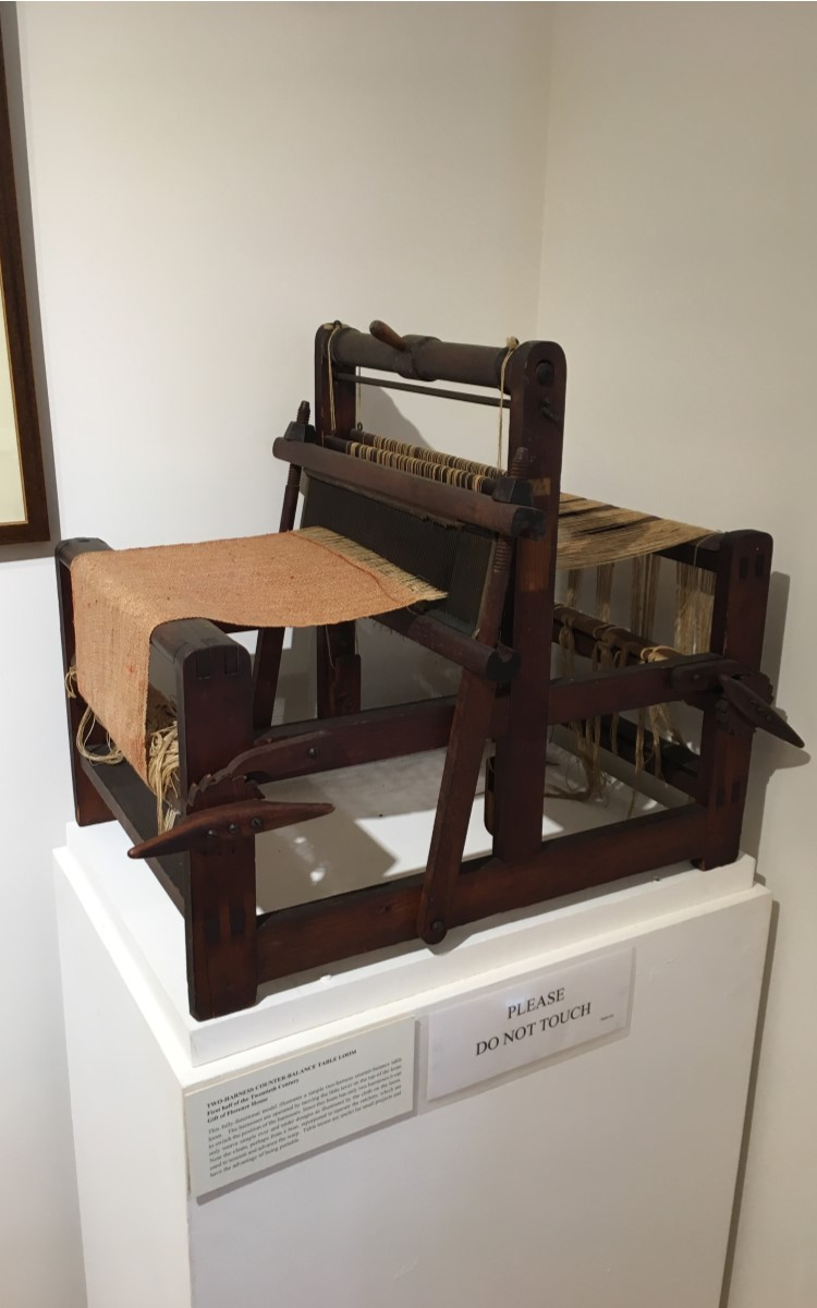 <h3>Two-Harness Counter-Balance Table Loom</h3> <br> <p><strong>First half of the Twentieth Century</strong></p> <p><strong>Gift of Florence House</strong></p> <br> <p>This fully-functional model illustrates a simple two-harness counter-balance table loom. The harnesses are operated by moving the little lever on the top of the loom to switch the position of the harnesses. Since this loom has only two harnesses it can only weave simple over and under designs as illustrated by the cloth on the loom. Note the cleats, perhaps from a boat, repurposed to operate the ratchets, which are used to tension and advance the warp. Table looms are useful for small projects and have the advantage of being portable.</p>