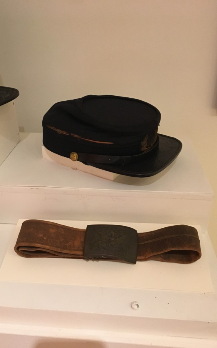 """<h3>Forage Cap</h3> <br> <p><strong>Maker unknown</strong></p> <p><strong>1860s</strong></p> <br> <p>Civil War headgear of this type, known as forage caps, were issued to Union soldiers throughout the war. The height and decoration can vary, but the basic shape remained constant throughout the Civil War. The original type is the taller version with its signature forward sloping top and smallish visor. The shape derived from the shako – the tall headgear that was part of virtually every military in Europe and America. The shako is still in use for military dress parades in many countries – usually with the addition of plumes or other decoration. Most Civil War forage caps were more comfortable than the earlier shako as they usually had the stiffening removed – but were considered by some to be as """"shapeless as a feed bag."""" They are not particularly practical as the visor did not shield the sun to any great degree, and the fabric certainly did not repel the rain or stop bullets. Variations on size, shape, and decoration were sometimes named after a particular officer who styled and wore his own singular version. The over-all look, however, remained the same. Most are dark blue, usually wool or wool/cotton blend, with a stiff, black visor. This shorter version – still with the forward sloping angle – is often known as a kepi.</p> <br> <br> <hr> <br> <br> <h3>Civil War Uniform Belt</h3> <br> <p><strong>1860s</strong></p> <p><strong>Gift of Elbert Tabor</strong></p> <br> <p>It is unusual for the leather portion of the belt to survive.</p>"""