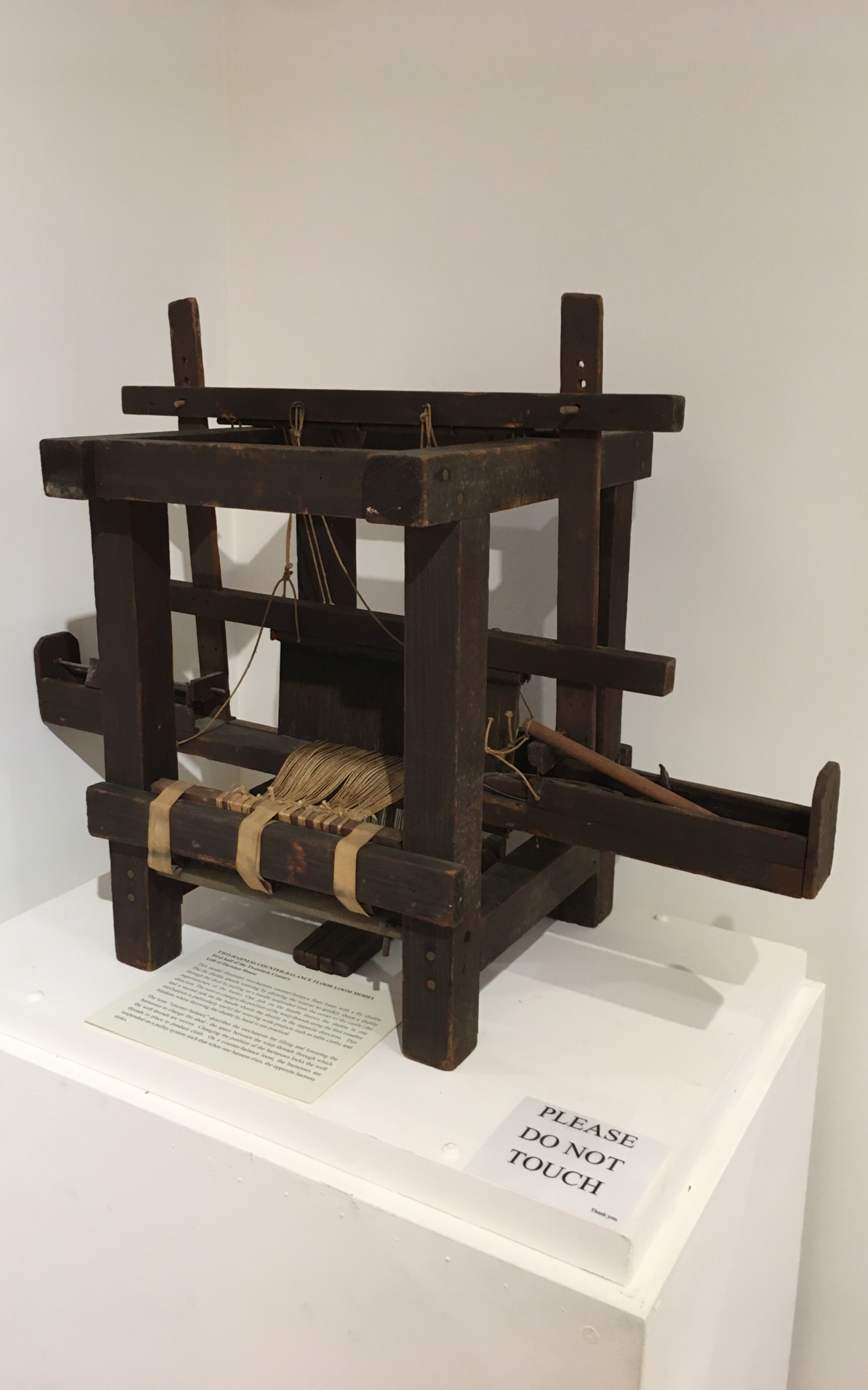 """<h3>Two-Harness Counter-Balance Floor Loom Model</h3> <br> <p><strong>First half of the Twentieth Century</strong></p> <p><strong>Gift of Florence House</strong></p> <br> <p>This model illustrates two-harness counter-balance floor loom with a fly shuttle. The fly shuttle speeds weaving by allowing the weaver to quickly shoot a shuttle through the shed by pulling on a handle suspended from the center of the castle (the superstructure of the loom). One jerk on the handle throws the shuttle in one direction. The weaver changes the position of the warp threads using the foot treadles and a second jerk on the handle shoots the shuttle in the opposite direction. This mechanism is particularly useful for weaving wide projects such as table cloths and blankets where throwing the shuttle by hand is not practical. The term """"counter-balance"""" describes the mechanism for lifting</p>"""