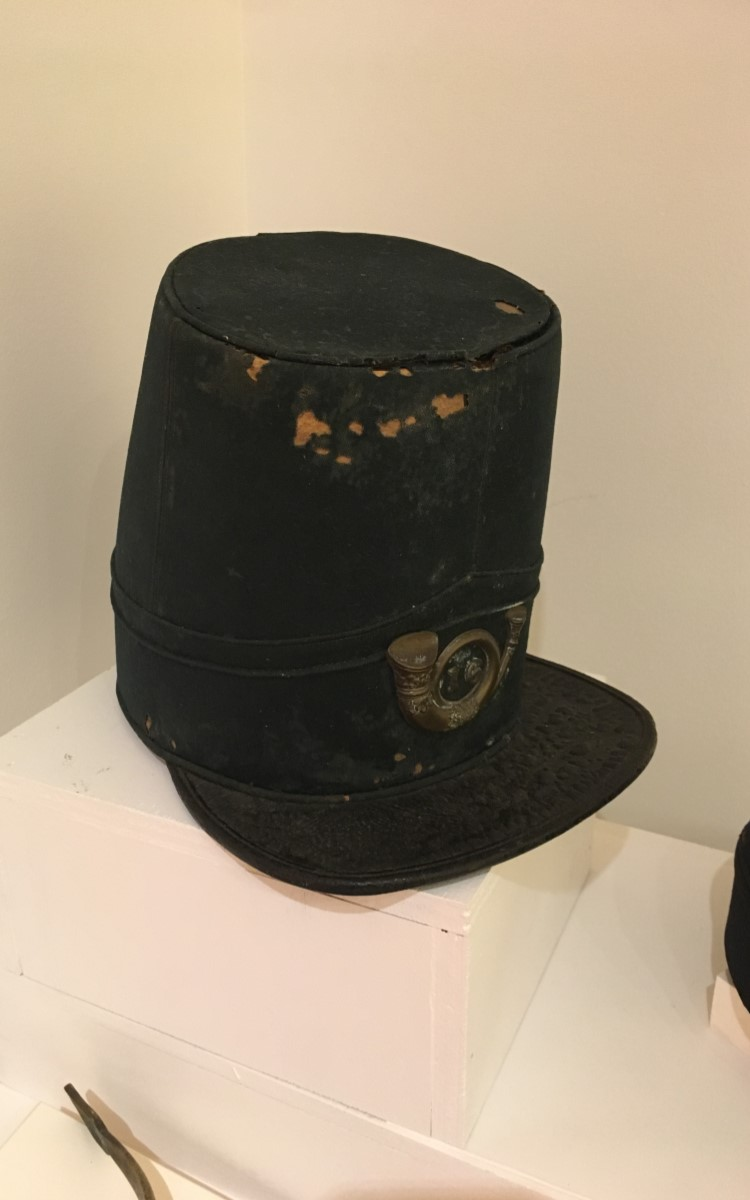 """<h3>Forage Caps</h3> <br> <p><strong>Maker unknown</strong></p> <p><strong>1860s</strong></p> <br> <p>Civil War headgear of this type, known as forage caps, were issued to Union soldiers throughout the war. The height and decoration can vary, but the basic shape remained constant throughout the Civil War. The original type is the taller version with its signature forward sloping top and smallish visor. The shape derived from the shako – the tall headgear that was part of virtually every military in Europe and America. The shako is still in use for military dress parades in many countries – usually with the addition of plumes or other decoration. Most Civil War forage caps were more comfortable than the earlier shako as they usually had the stiffening removed – but were considered by some to be as """"shapeless as a feed bag."""" They are not particularly practical as the visor did not shield the sun to any great degree, and the fabric certainly did not repel the rain or stop bullets. Variations on size, shape, and decoration were sometimes named after a particular officer who styled and wore his own singular version. The over-all look, however, remained the same. Most are dark blue, usually wool or wool/cotton blend, with a stiff, black visor.</p>"""