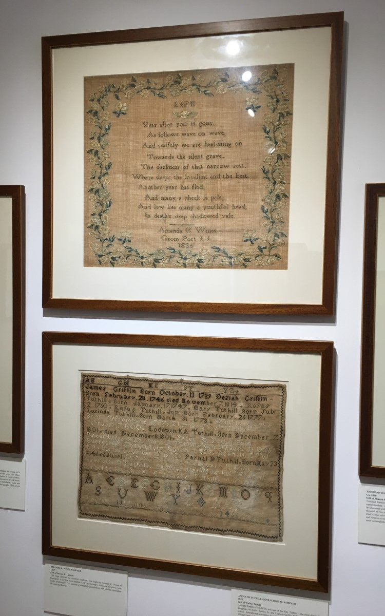 """<h3>Amanda K. Wines Sampler</h3> <br> <p><strong>1835</strong></p> <p><strong>Gift of George R. Latham</strong></p> <br> <p>This large sampler, in excellent condition, was made by Amanda K. Wines of Greenport. A ten-line poem entitled """"Life"""" is followed by her name, the place it was made, and the date. This sampler is beautifully embroidered with a border decoration of vines and flowers.</p> <br> <br> <hr> <br> <br> <h3>Asenath Tuthill Genealogical Sampler</h3> <br> <p><strong>1823</strong></p> <p><strong>Gift of Walter Tuthill</strong></p> <br> <p>Asenath Tuthill (1810-1875) was one of the Tiny Tuthills – the three diminutive daughters of Rufus Tuthill, Jr. and Lucinda Griffin Tuthill (Augustus Griffin's sister). Asenath and her sisters, Cynthia and Lucretia, lived together in a house on Village Lane and supported themselves as expert seamstresses. Asenath made this as a gift to her elder sister Cynthia (1797-1881). The two lines above the lower alphabet read: <em>Asenath E. Tuthill's Sampler Mark'd by her While at School to her Sister Cynthia A. Tuthill. August 25, 1823</em>. The sampler has the usual alphabet at the top and repeated (in both upper case and lower case) at the bottom. It is mostly a genealogical sampler of her family – both Griffins and Tuthills. For that reason, it is an important Oysterponds document - as well as being a fine example of a young girl's needlework. Asenath has framed her sampler with a simple zig-zag border.</p>"""